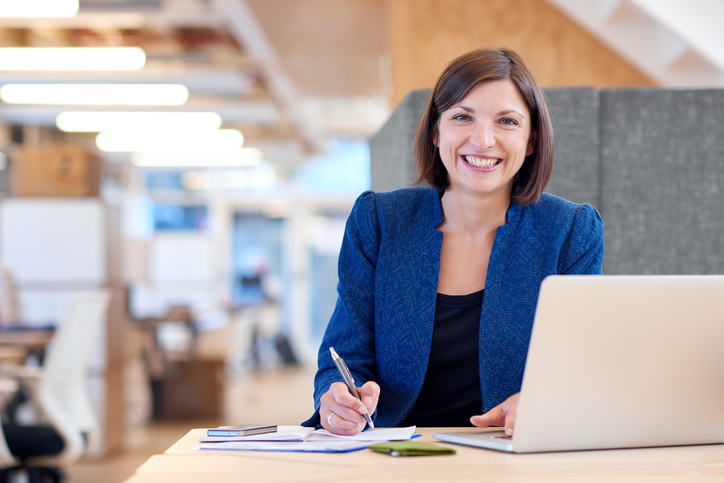Busineswoman smiling broadly while working in her office cubicle